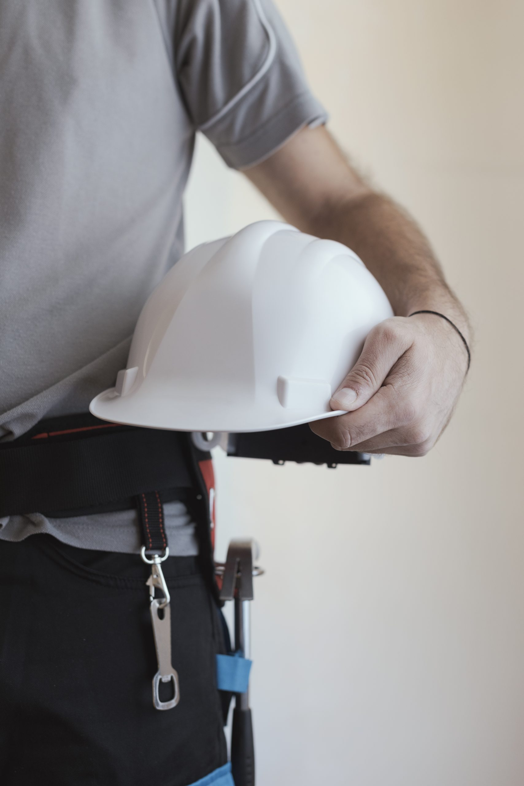 Construction worker holding a safety helmet: construction and workplace safety concept