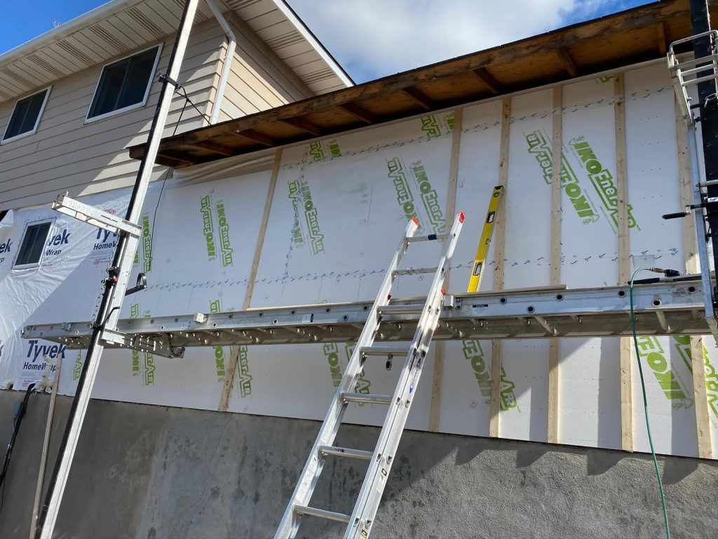 Image of the exterior of a house that is under construction with a ladder leaning next to it.