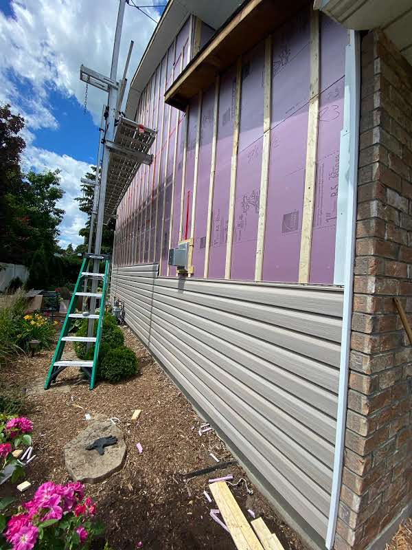 Image of a house with new siding half way up. Appears to be in the middle of renovations.