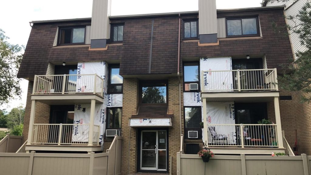 Small apartment building is currently under construction as it gets replacement siding.