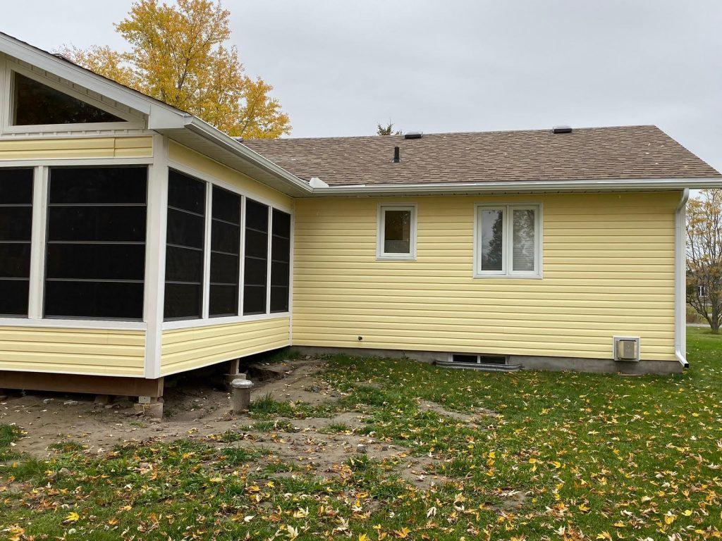 Image of a bungalow with yellow siding, big tinted windows, and white eavestroughs. Dark yellow and brown leaves have fallen onto the lawn in front of the house.