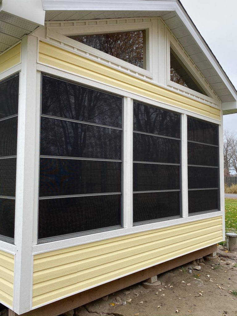 Close-up image of a new house with tinted windows, yellow siding, white eavestrough, and white soffit & fascia.